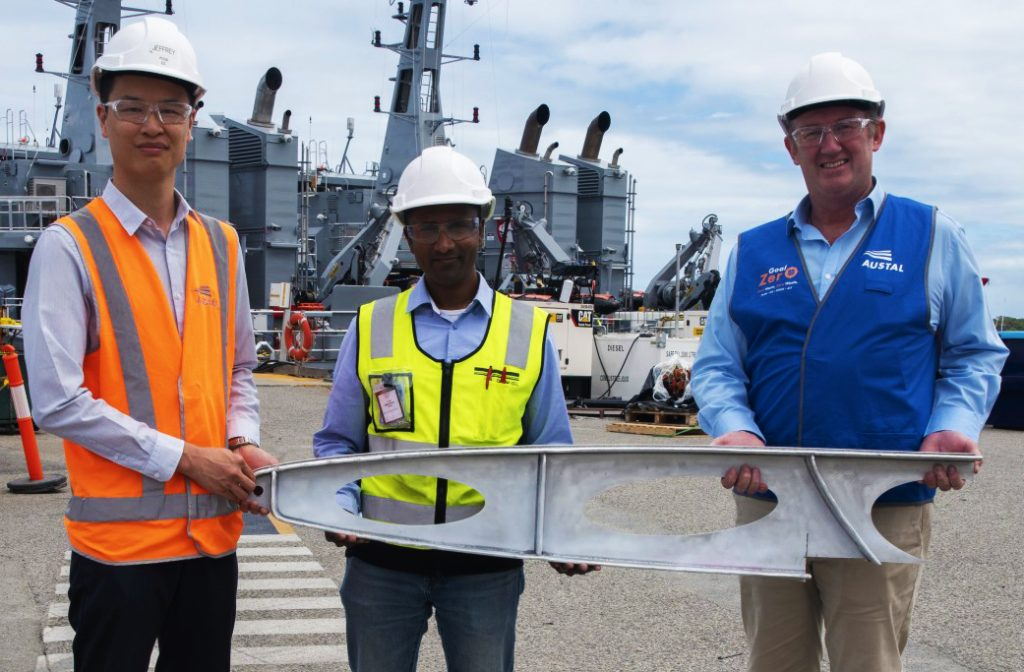 From Left: Austal Technology Project Manager, Jeffrey Poon, DNV Representative Jude Stanislaus, AML3D Chief Executive Officer Andrew Sales with a sample of the davit produced during the additive manufacturing project. (image: Austal Australia)